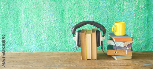Obraz na plátně audio book concept, with stacks of books, headphones and cup of coffee, panorama