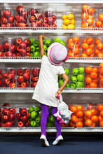 Young Girl Picking Fruits From Shelf In Supermarket
