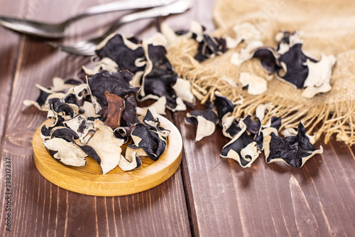 Lot of slices of dry black mushroom jew ear variety on round bamboo plate on bro Wallpaper Mural
