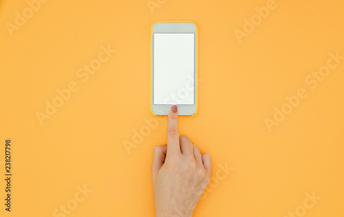 Fotografie, Obraz  Woman's hand unlocks a smartphone with a finger on the orange background