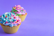 Closeup Two Colorful Cupcakes Decorated With Sprinkles In Shape Of Hearts On Purple Background With Copy Space.
