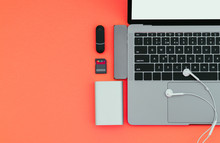 Laptop With USB Type-C Adapter, Flash Drives, Headphones And Power Bank On A Red Background, Top View, Workplace. Gadgets For Use A Modern Laptop. Technology Concept.