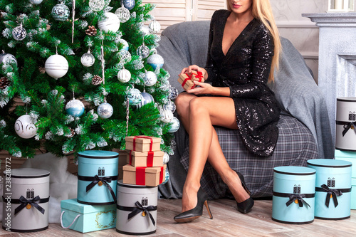 Obraz Woman with beautiful long tanned legs wearing black dress sitting in an armchair near by the christmas tree - fototapety do salonu