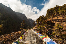 Everest Base Camp Trek. View Of The Himalayan Valley. Nepal. Bridge With Nepalese Prayer Flags Across The River. From Lukla To Namche Bazar