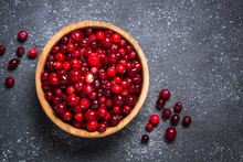 Cranberry In Wooden Bowl On Black Stone Background.
