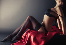 Sexy Young Brunette Woman In Black Sensual Lingerie And In Stockings Posing On Bed In Studio.