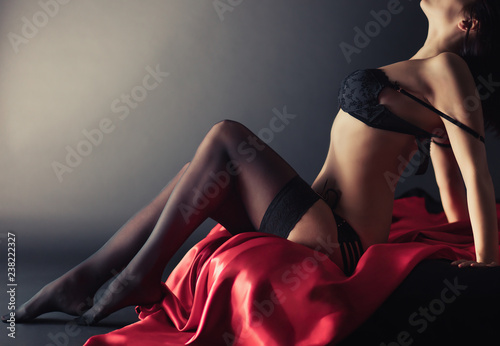 Sexy young brunette woman in black sensual lingerie and in stockings posing on bed in studio Wallpaper Mural
