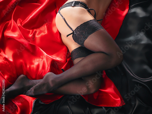 Fotografie, Obraz  Sexy young brunette woman in black sensual lingerie and in stockings using laptop on red bed in studio