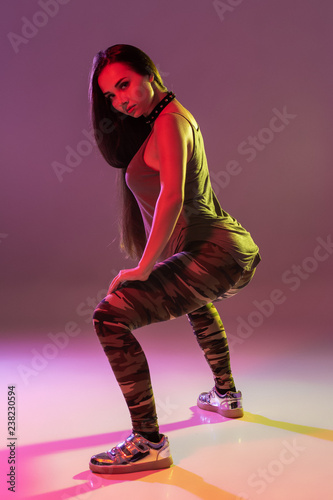 Fotografie, Obraz  Attractive young brunette woman in the studio dancing Booty dance on a dark back