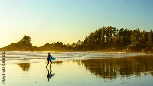 Tuinposter Centraal-Amerika Landen Ein Surfer geht an einem Strand auf Vancouver Island entlang