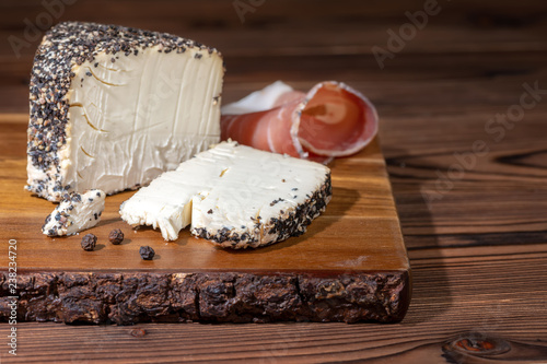 white cheese with grated black pepper and prosciutto on wooden cutting board