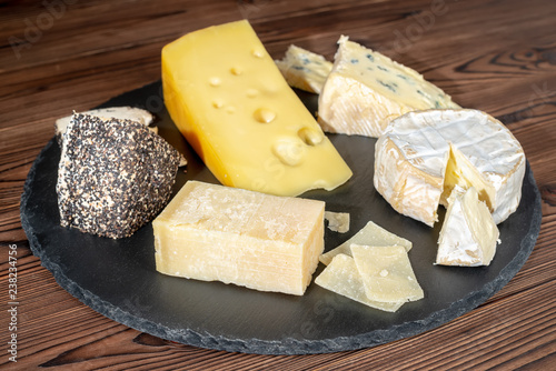 delicious various types of cheese on slate stone background