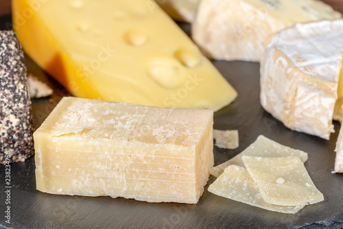 portion and slaced of fresh parmesan cheese and various types of cheese on black slate, close up
