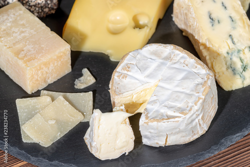 portion of fresh white cheese with mold and various types of cheese on black slate texture, close up