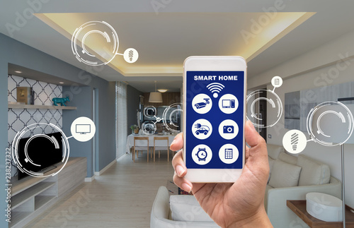 Fotografia  Hand holding smart phone showing the smart home control screen and icon over the