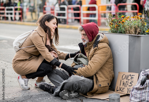 Young woman giving money to homeless beggar man sitting in city. Fototapete