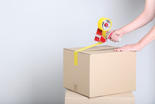 Female Hands Packaging Cardboard Box With Dispenser On Grey Background