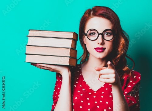 Portrait of redhead woman with books on blue background
