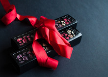 Macaroon On Black Background With Red Ribbon, Colorful Almond Cookies, Pastel Colors.