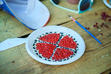 Handmade Design Of A Plastic Plate With Seeds Colored In Red And White