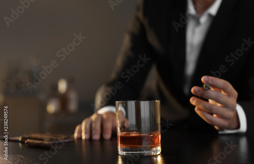 Poster Cocktail Man with glass of whiskey and cigar sitting at table, closeup. Space for text