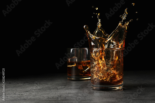 Photo Splashing golden whiskey in glass with ice cubes on table