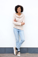 Full Body Smiling African American Woman With Arms Crossed Against White Wall