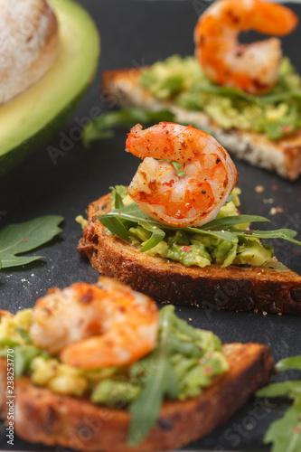 Appetizer of bread with seeds, shrimp, avocado and arugula. Crostini. Bruschetta. Sandwich. Antipasti. Selective focus