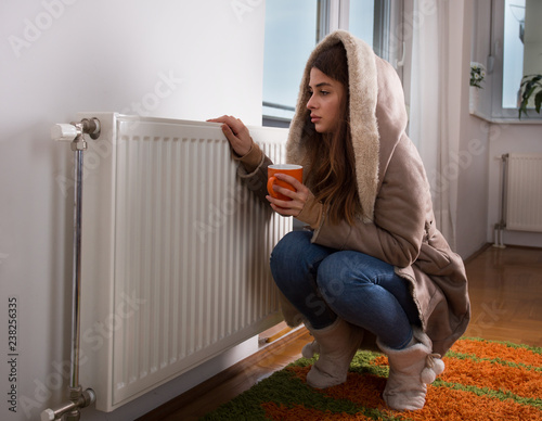 Canvas Print Girl in jacket beside radiator at home