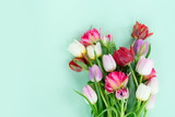 Bunch of fresh tulips flowers on pastel green background with copy space