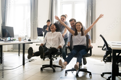 Plakaty do biura happy-multiracial-colleagues-group-having-fun-together-riding-on-chairs-in-office-diverse-excited-office-workers-enjoying-break-laughing-engaged-funny-activity-celebrating-corporate-success