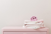 A Pile Of Clean Ironed Bedding And A Towel Lies On The Dresser.
