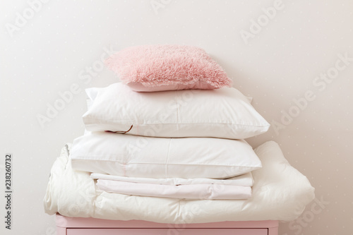 Fotografía  A pile of clean ironed bedding and a towel lies on the dresser.