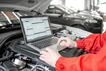 Auto Mechanic Diagnosing Car Engine With A Laptop With Special Program, Close-up View With No Face
