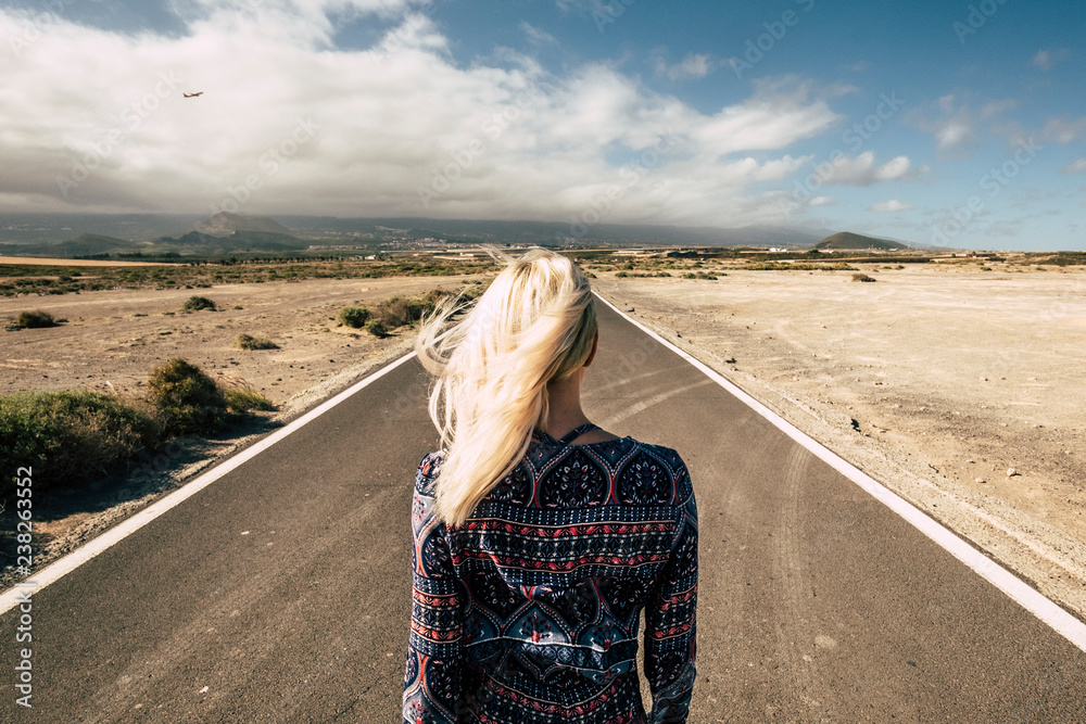 Fototapeta travel and future choiches concept with blonde young millennial girl viewed from rear walking on a straight long road - airplane fly in the background - people moving and enjoying the world concept
