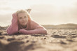 Attractive lady lay down at the beach on the sand in winter or autumn season with a pink sweater enjoying the outdoor relaxed activity alone with no people around -millennial girl feel the world