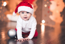 Funny Baby Boy Wearing Santa Hat Over Christmas Lights In Room. Looking At Camera. Winter Holidays.
