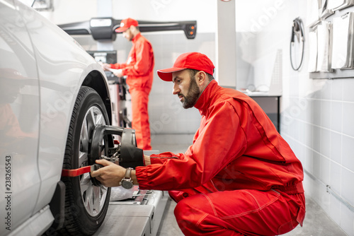 Photo Handsome auto mechanic in red uniform fixing disk for wheel alignment at the car