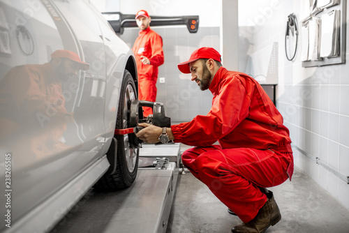 Handsome auto mechanic in red uniform fixing disk for wheel alignment at the car Canvas Print