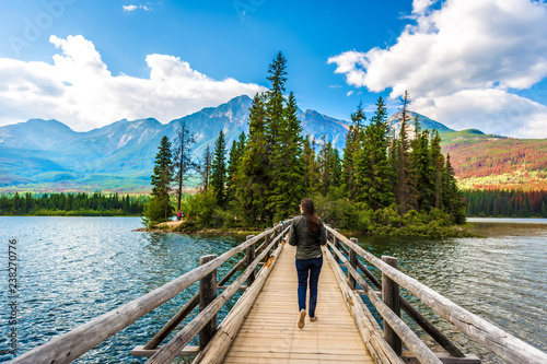 Valokuva  Young woman walking in a narrow wood bridge in front of an amazing scenario in J