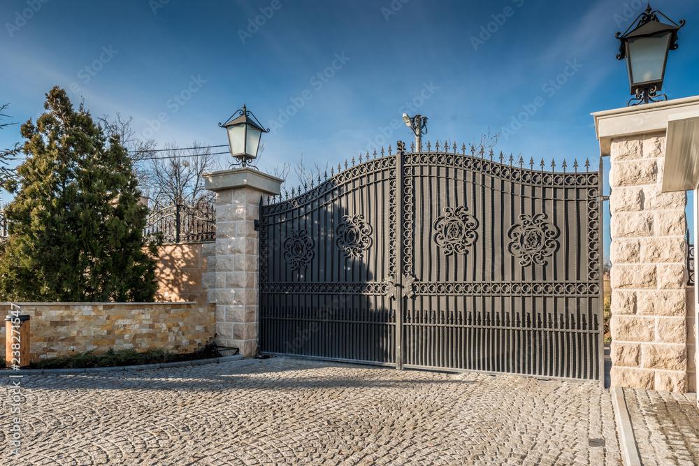 Fototapeta Metal driveway security entrance gates set in brick fence