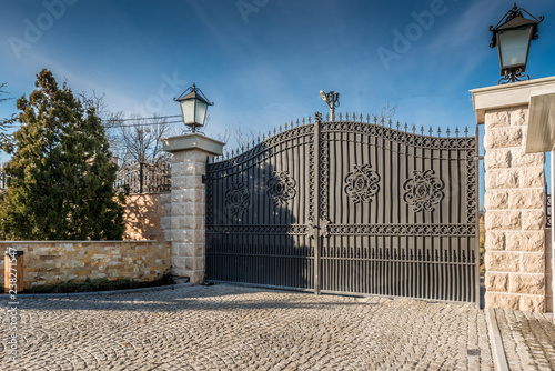 Fototapeta Metal driveway security entrance gates set in brick fence