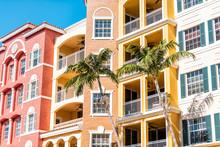 Condos, Condominiums Colorful, Orange Yellow Multicolored Buildings Facade Exterior With Windows, Palm Trees, Real Estate Property In Spain