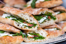 Closeup Of Fresh Display Of Stacked Pile Of Panini Bread, Mozzarella Melted Cheese, Vegetarian Italian Tomatoes, Basil Lettuce In Store, Shop, Cafe Buffet Catering Sandwiches