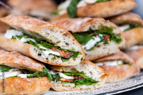 Fototapeta Closeup of fresh display of stacked pile of panini bread, mozzarella melted cheese, vegetarian italian tomatoes, basil lettuce in store, shop, cafe buffet catering sandwiches obraz