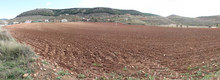 A Landscape Of Brown Earth Plowed Fields In Autumn With Some Farms On The Background Among The Hills Of Monterde Rural Town In Aragon Region, Spain