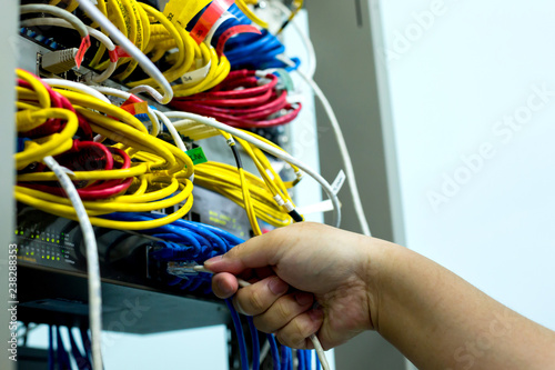 A hand holding LAN cord with Ethernet cables and Network switching hub LAN System Communication