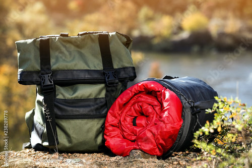 Obraz Backpack and sleeping bag on ground outdoors. Camping equipment - fototapety do salonu