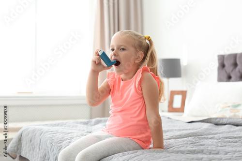 Little girl using asthma inhaler in bedroom Wallpaper Mural
