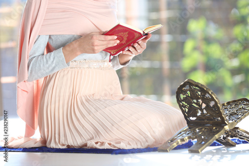 Muslim woman reading Koran on prayer mat indoors, closeup